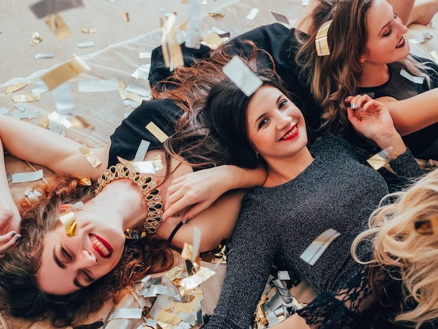 파티 소녀. 재미와 기쁨. 반짝이 색종이. 검은 침대에서 편안한 젊은 여성. 축제 분위기와 장식. 이빨 미소.
