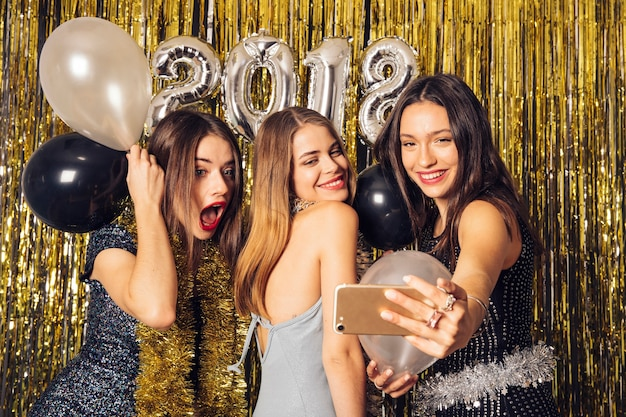 Le ragazze del partito prendono selfie sul partito di nuovo anno
