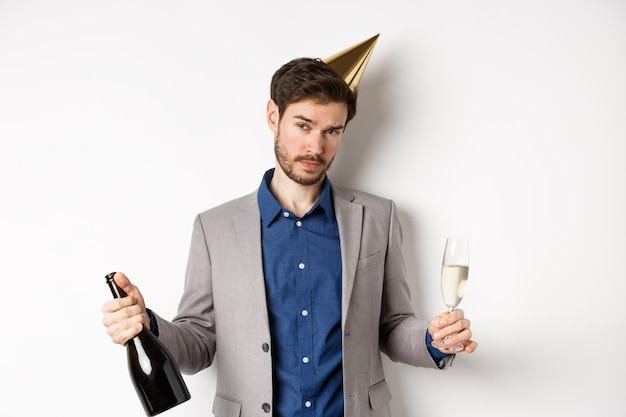 Party guy standing in birthday hat and celebrating, holding champagne bottle and glass