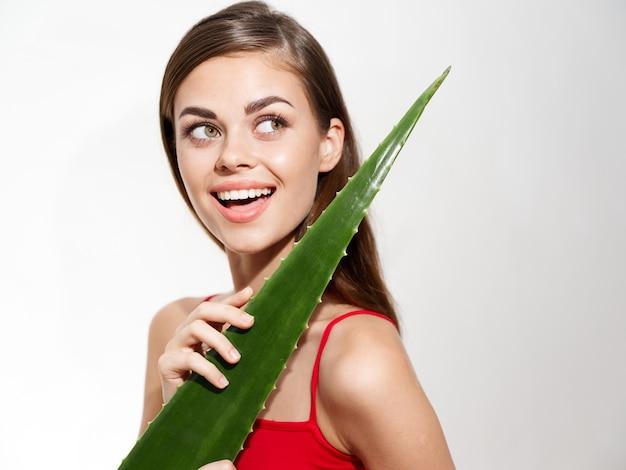 明るい背景とトリミングされたビューモデルに緑のアロエの葉を持つパーティー幸せな女性