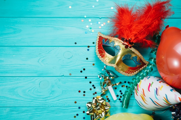파티 용 모자; 색종이와 나무 테이블에 황금 무도회 카니발 마스크 풍선