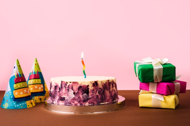 Party hat; birthday cake and stack of gift boxes on desk against pink background
