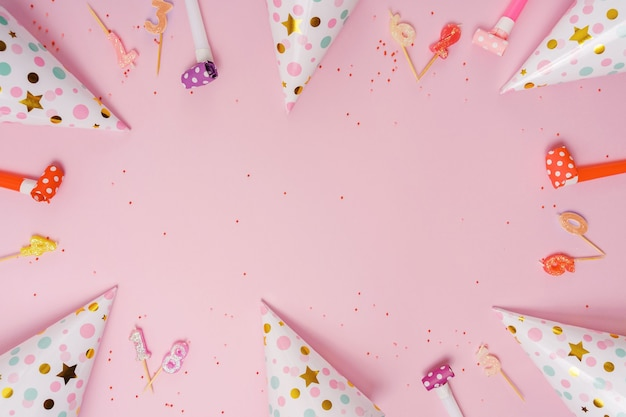 Party hat and candles lying on pink background.