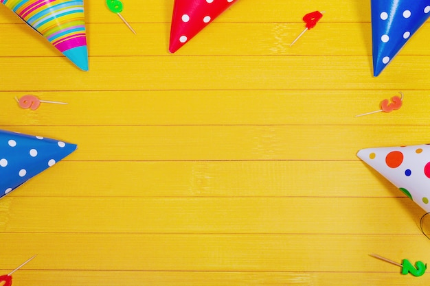 Party hat and candles on yellow wooden background.