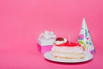 Party hat; gift box and slice of cake with candle on pink background