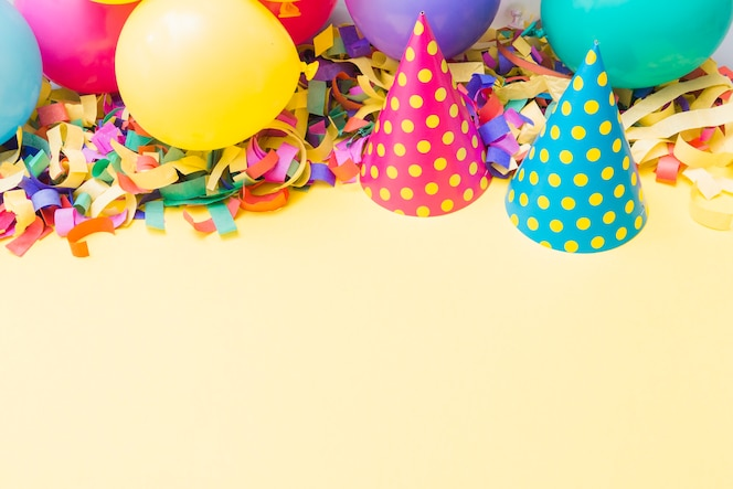 Party hats near balloons on confetti