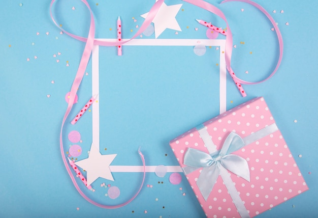 Party holiday surface with ribbon, stars, birthday candles, gift box empty frame and confetti on blue surface