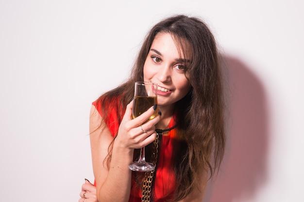 パーティー、休日、お祝いのコンセプト-シャンパンやワインを飲み、白い背景の上で踊る赤いドレスの陽気な魅力的な若い女性。