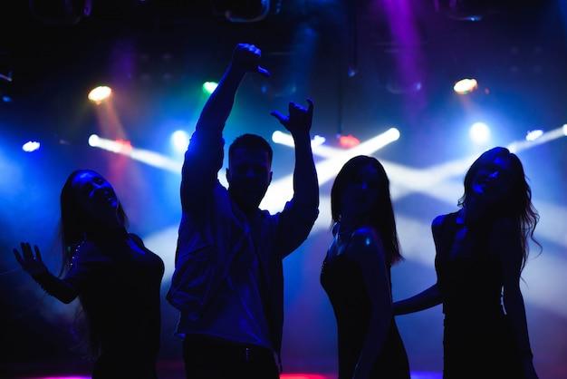 Партия, праздники, праздники, ночная жизнь и люди концепции - группа счастливых друзей, танцующих в ночном клубе