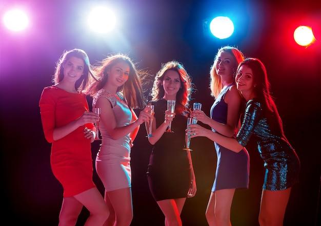 파티, 휴일, 축하, 밤문화 및 사람들의 개념 - 웃고 있는 아름다운 소녀들이 춤을 추고 있습니다.