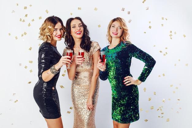 Concetto di festa e vacanze. tre donne glamour in lussuose paillettes glitterate si vestono bevendo cocktail e divertendosi