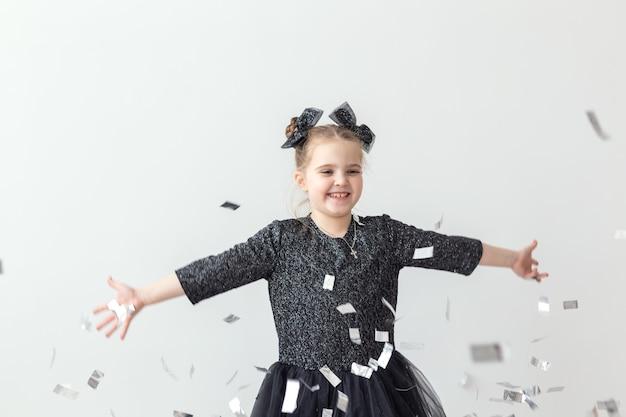 パーティー、休日、新年、お祝いのコンセプト-紙吹雪を投げる女性の子供。