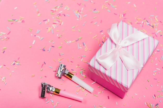 Party horns and closed gift box with colorful sprinkle on pink background