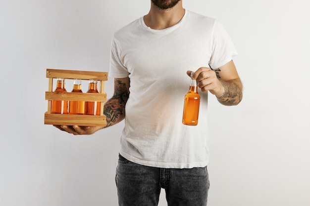 A party host in plain cotton t-shirt and dark denim shorts holding a pack of craft fruit beer and offering one isolated on white