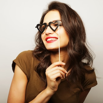 Party image. playful young woman holding a party glasses. ready for good time.