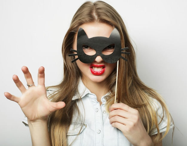 Party image. playful young woman holding a party mask.