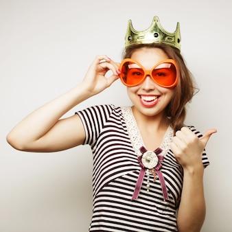 파티 이미지입니다. 큰 파티 안경과 왕관을 쓴 쾌활한 젊은 여성. 좋은 시간을 위한 준비.