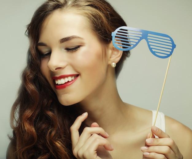 パーティーのイメージ。パーティーメガネを保持している遊び心のある若い女性。