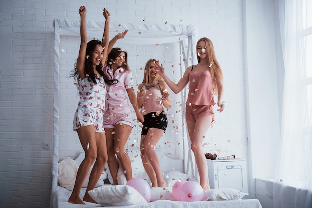 The party is in full swing. confetti in the air. young girls have fun on the white bed in nice room