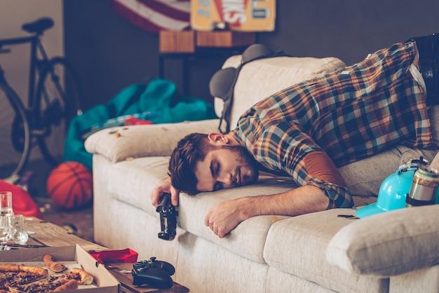 Вечеринка окончена. молодой красавец потерял сознание на диване с джойстиком в руке в грязной комнате