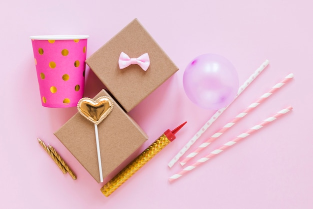 Party items on pink background top view
