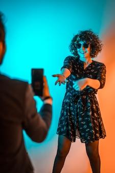 Праздничный образ жизни, молодой человек записывает видео молодой женщины, танцующей на вечеринке с оранжевыми и синими огнями