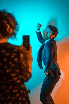 Праздничный образ жизни, молодая женщина записывает видео молодого человека, танцующего на вечеринке с оранжевыми и синими огнями