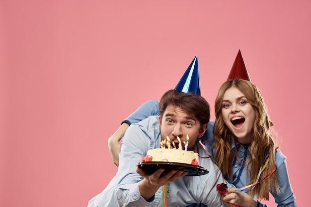 パーティーの男性と女性の企業のピンクの壁の楽しいケーキキャップ。