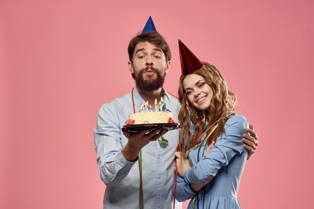 Party man and woman with cake on pink background corporate birthday