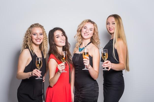 パーティー、新年、人々のコンセプト-パーティーでシャンパングラスをチリンと鳴らす陽気な若い女性。