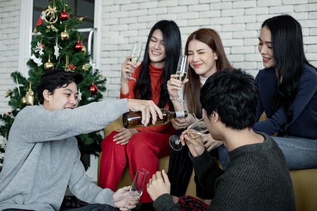 Вечеринка группы молодых азиатских с разливанием вина для питья дома в праздновании рождества. празднование нового года дома. веселого рождества и счастливых праздников тайской банды подростка.