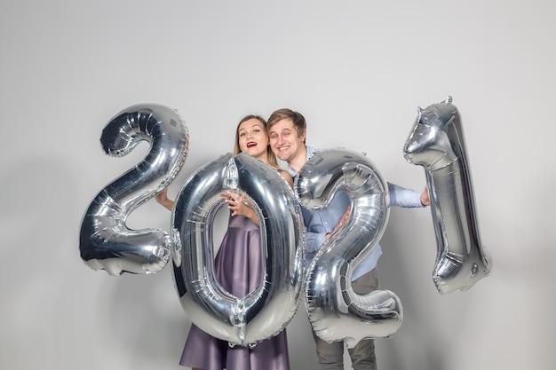 Концепция вечеринок, людей и новогодних праздников - женщина и мужчина празднуют канун нового года 2021 года.