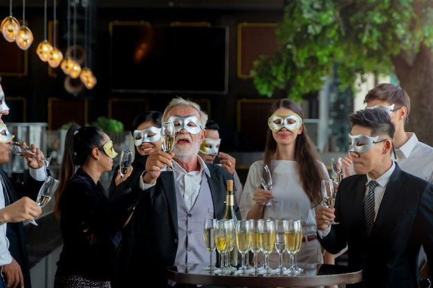 Party people fancy mask of executive business team picking up wine glass for drinking and talking to celebrate.