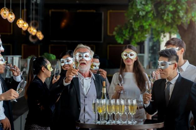 파티 사람들은 술을 마시고 축하하기 위해 와인 잔을 집어 드는 임원 비즈니스 팀의 멋진 마스크입니다.