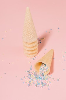 Party sprinkles balls spilling from waffle cone against pink background