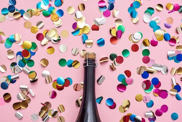 パーティーはピンクの背景にきらびやかな紙吹雪でシャンパンのボトルを開始しました