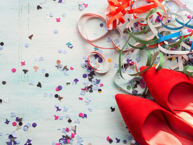 Party symbols flat lay with red shoes