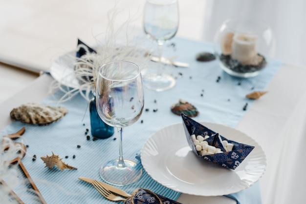 Сервировка стола в морском стиле. элегантные тарелки, стаканы, в голубых тонах. бумажные кораблики с зефиром. день рождения или концепция детского душа мальчика.