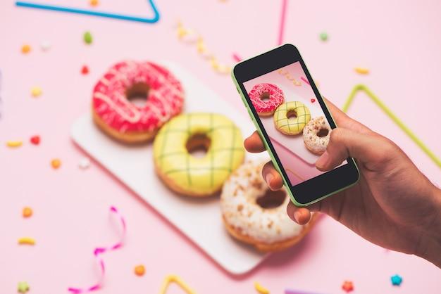 파티. 다른 다채로운 설탕 둥근 글레이즈드 도넛의 사진 찍기