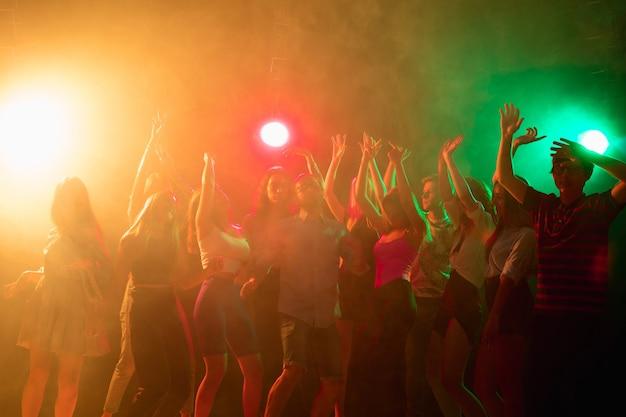 파티 타임. 실루엣의 사람들이 손을 들고 네온 불빛 배경의 댄스플로어에서 춤을 춥니다. 나이트 라이프, 클럽, 음악, 댄스, 모션, 젊음. 밝은 색상과 움직이는 소녀와 소년.