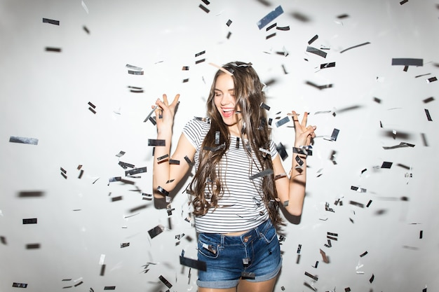 Party time. cheerful young woman stretching out her hands while confetti falling on her