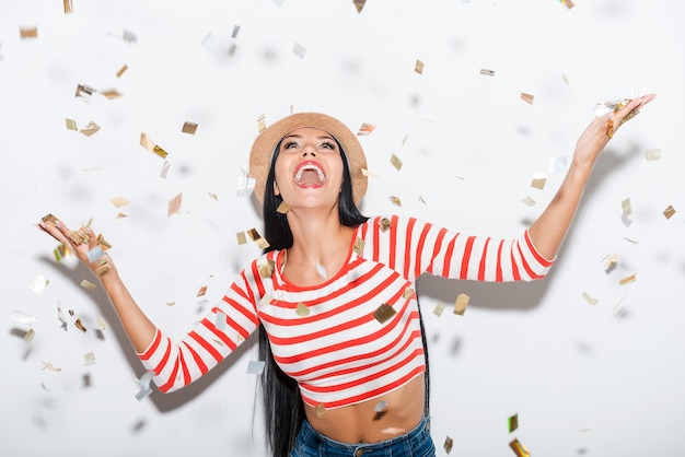 Party time! cheerful young woman stretching out her hands while confetti falling on her