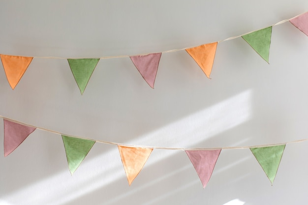 Party time - colorful garland made of triangular textile flags hanging on white wall background