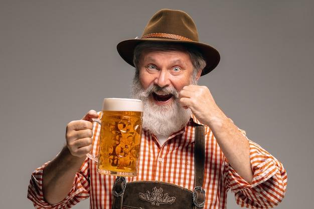 パーティーの時間。灰色のスタジオの背景にビールのジョッキと伝統的なオーストリアまたはバイエルンの衣装を着た幸せな年配の男性。コピースペース。お祝い、オクトーバーフェスト、お祭り、伝統のコンセプト。