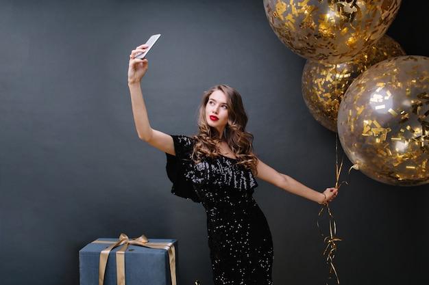긴 곱슬 갈색 머리가 황금 반짝이로 가득한 큰 풍선 셀카를 만드는 검은 명품 드레스에 젊은 매력적인 여자의 파티 시간. 선물, 축하, 현대.