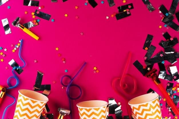 Партия мишура и красочные чашки крупным планом на фиолетовом фоне