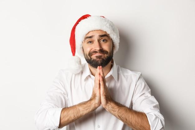パーティー、冬休み、お祝いのコンセプト。クリスマスプレゼントを物乞い、懇願し、何かを求めてサンタ帽子をかぶった大人の男のクローズアップ