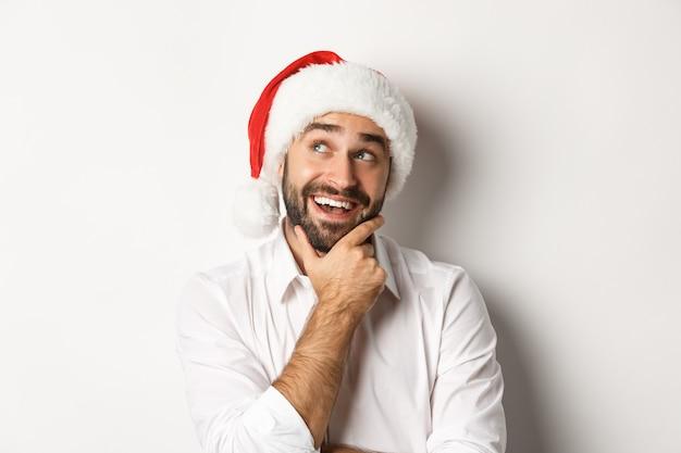 Партия, зимние праздники и концепция празднования. крупный план счастливого человека, планирующего список рождественских подарков, в шляпе санта, глядя на вдумчивый, белый фон в верхнем левом углу.