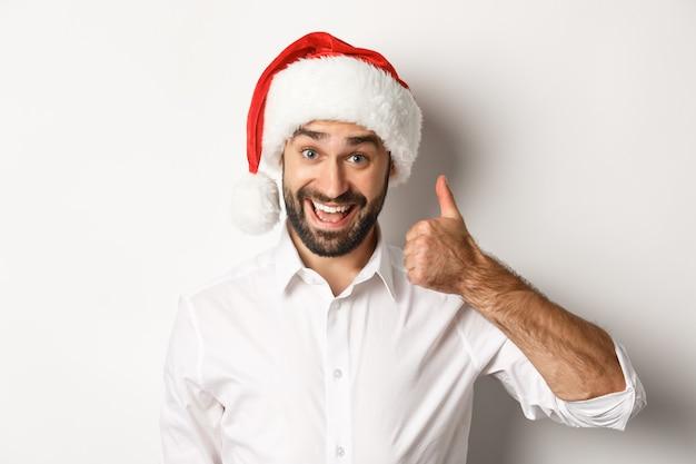 パーティー、冬休み、お祝いのコンセプト。サンタの帽子をかぶった満足のいくひげを生やした男のクローズアップは、親指を立てて、承認し、何か良いものが好きです