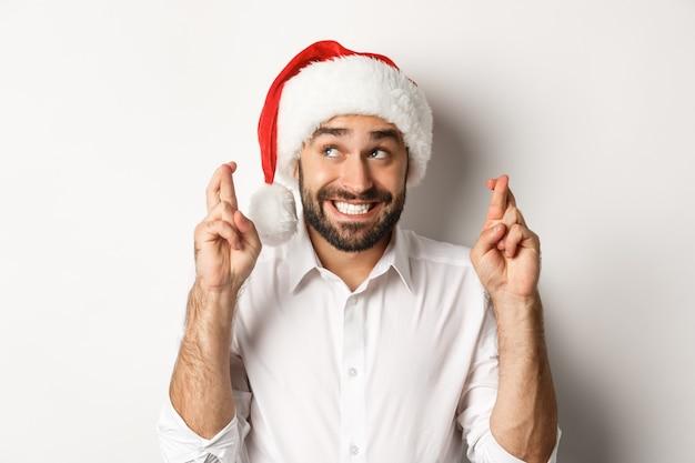 パーティー、冬休み、お祝いのコンセプト。クリスマスの願い事をするサンタの帽子をかぶった幸せな男、幸運と笑顔のために指を交差させて興奮